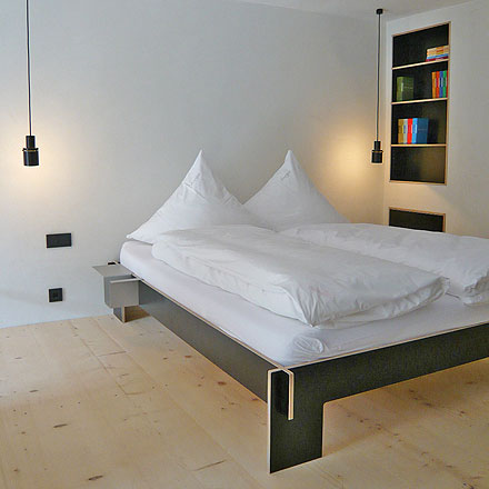 black pendant lights over bed